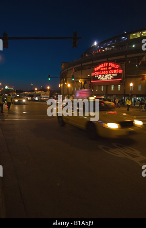 A taxi cab rushes by Wrigley Field as the Cubs play a night game at the famous stadium in Chicago, IL. - Stock Photo