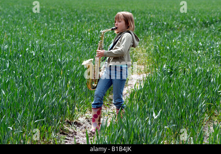 Little girl playing the saxophone in a field of crops Walking through the English countryside - Stock Photo