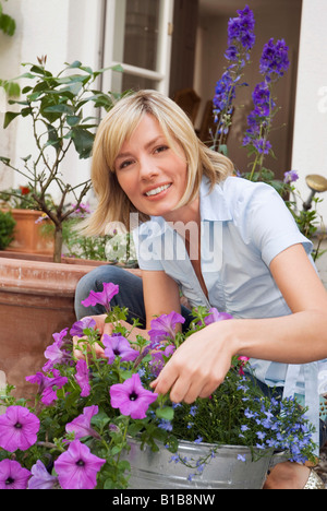 Young woman planting flowers, outdoors - Stock Photo