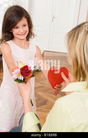 Girl (8-9) giving her mother a gift - Stock Photo