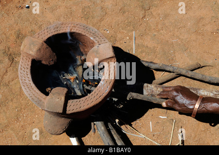 African woman lighting up fire in a terracotta stove - Stock Photo