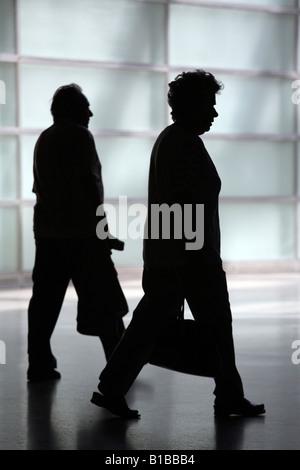 Silhouette of an elderly couple walking apart - Stock Photo