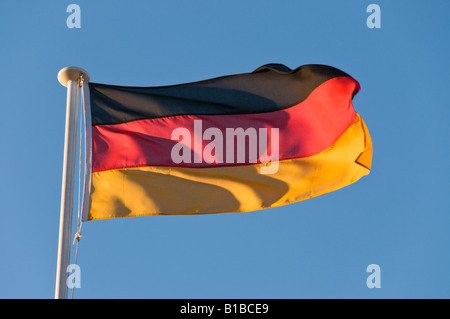 A German Flag Blowing In the Wind On A Blue Sky Background - Stock Photo