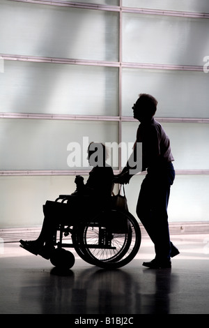 Silhouette of an elderly woman in a wheelchair and her carer - Stock Photo