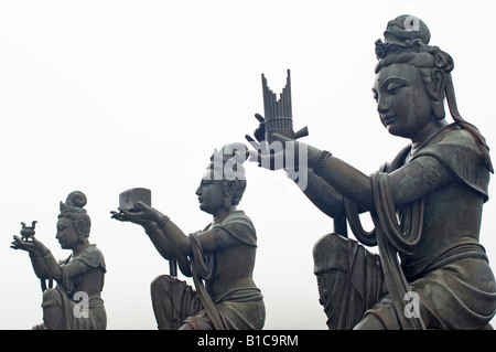 Buddhist statues making offerings to the Tian Tan Buddha on a misty day. Po Lin Monastery, Ngong Ping, Lantau Island, - Stock Photo