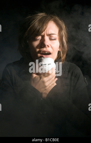 Woman in medical mask inside clouds of smoke - Stock Photo