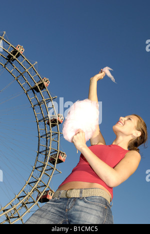 happy young woman with candy floss in front of the Wiener Riesenrad auf dem Prater, Austria, Vienna - Stock Photo