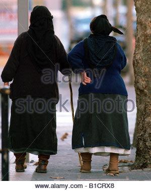 TWO 2 Old GREEK WOMEN WITH STICK WALKING ALONG REAR VIEW FULL LENGTH WALK GREECE woman senior back rear full length - Stock Photo