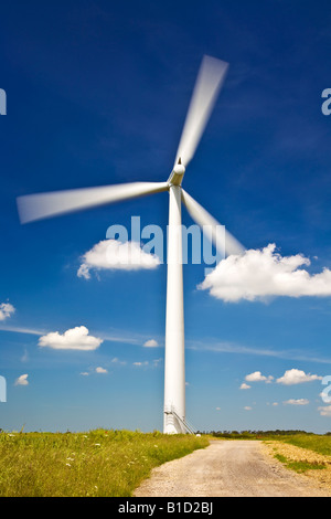 Single wind turbine with blades turning against a deep blue summer sky on an inshore wind farm in Oxfordshire, England, UK