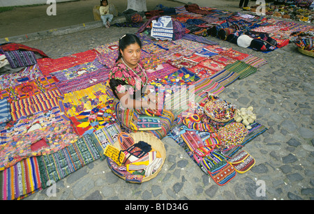 A Mayan Indian woman wearing a traditional huipil sells weavings in the city of Antigua in the highlands of Guatemala - Stock Photo
