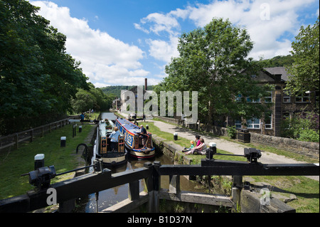 Narrowboats about to exit the lock gates on the Rochdale Canal, Hebden Bridge, Calder Valley, West Yorkshire, England - Stock Photo