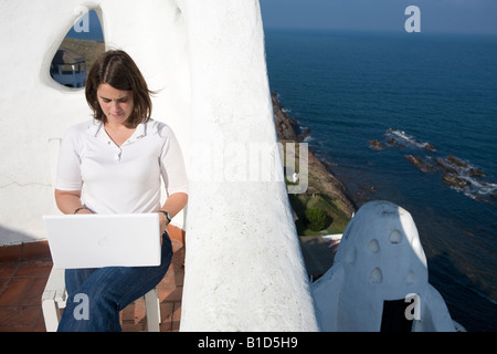 Young woman writting on her macbook laptop in a mediterranean terrace in Casapueblo Punta del Este Uruguay - Stock Photo