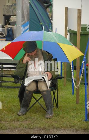 Farmer Sitting Under Umbrella Royal Welsh Show - Stock Photo