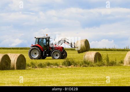 Massey Ferguson farm tractor transporting straw bale, France. - Stock Photo