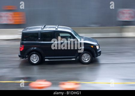 An SUV drives on a city street in New York - Stock Photo