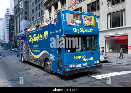A City Sights NY tour bus on Broadway in Lower Manhattan, NY. - Stock Photo