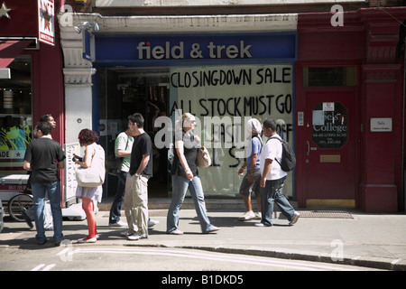 Shop closing down sale window with people walking past on pavement London - Stock Photo