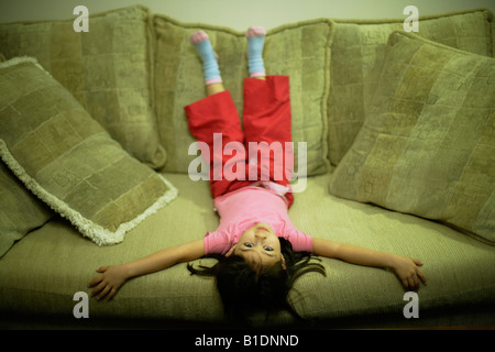 Four year old girl lies back on large sofa - Stock Photo