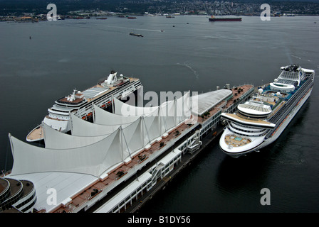 Aerial view of two cruise ships in Canadian city Harbour coming into dock at Canada Place cruise ship terminal - Stock Photo