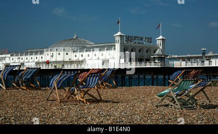 Brighton Pier, beach and deckchairs. - Stock Photo