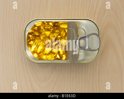 Fish oil capsules in a ring pull tin. Plan view on wooden surface - Stock Photo