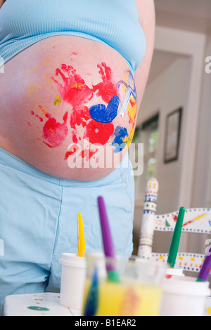 Close up of pregnant woman's belly covered with finger painting from daughter Alaska United States - Stock Photo