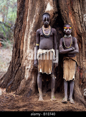 Two young Karo girls stand in front of the massive trunk of a fig tree.  A small Omotic tribe related to the Hamar. - Stock Photo