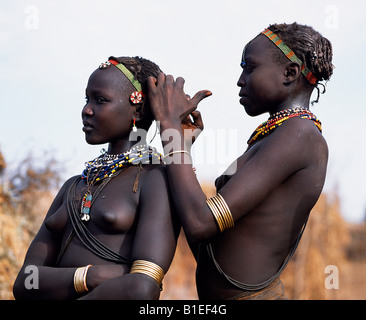 A Dassanech girl braids her sister's hair at her village in the Omo Delta.  Much the largest of the tribes in the - Stock Photo