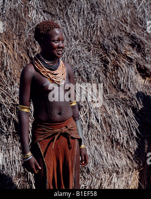 A Nyangatom woman with ornamental scarring on her stomach.  The scars are made with a razor and then infected. - Stock Photo