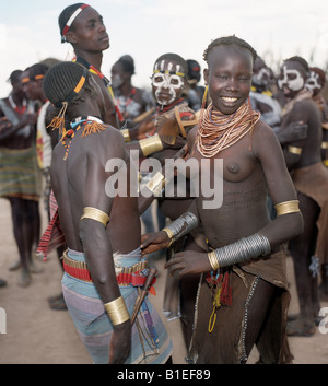 Young men and girls of the Karo tribe dance together. Every man carries a wooden stool, which doubles as a pillow - Stock Photo