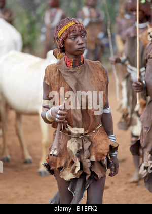 A Hamar woman holds a tin trumpet at a 'Jumping of the Bull' ceremony. The Hamar are semi-nomadic pastoralists. - Stock Photo