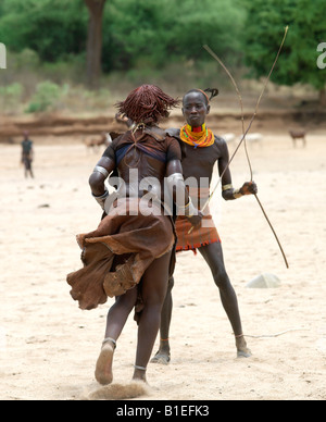 A Hamar woman being whipped by a man at a 'Jumping of the Bull' ceremony. The semi-nomadic Hamar of Southwest Ethiopia. - Stock Photo