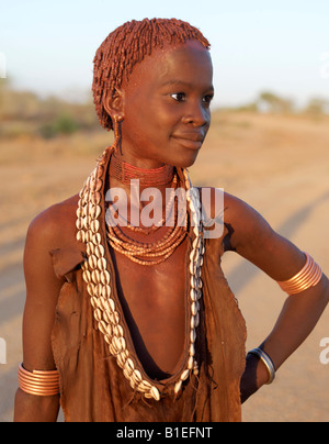 The ochre worn by a pretty young Hamar girl glows deep red in the late afternoon light.The Hamar are semi-nomadic - Stock Photo