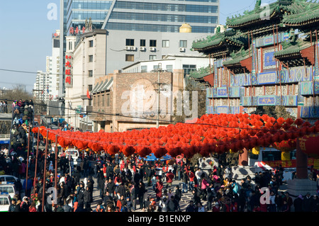 China Beijing Chinese New Year Spring Festival crowds of people walking under red lantern decorations at Ditan Park - Stock Photo