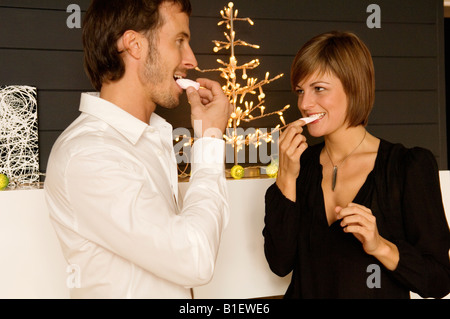 Mid adult man and a young woman eating candies - Stock Photo