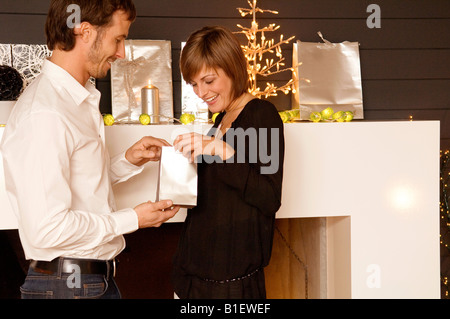 Side profile of a mid adult man giving a Christmas present to his wife - Stock Photo