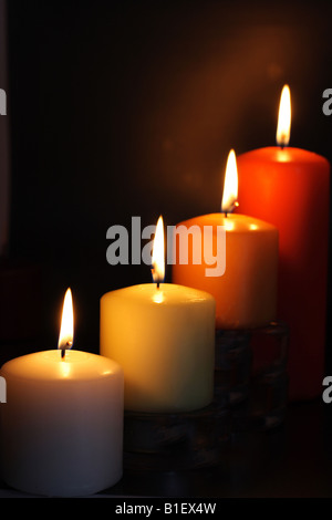 Four candles on black background - Stock Photo