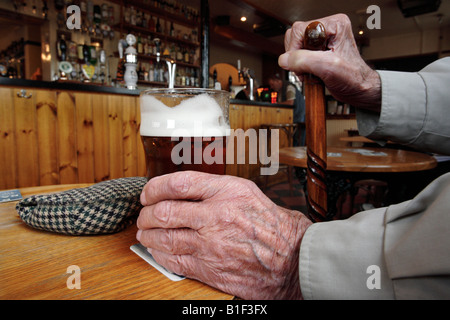 An old man holding a pint of bitter in a pub in Boston Lincolnshire UK - Stock Photo