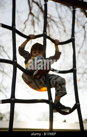 Six year old boy climbs on playground equipment New Zealand - Stock Photo