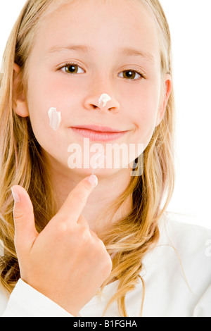 young blonde girl with face cream - Stock Photo