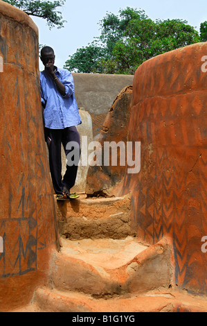 Young local man in a narrow lanes between the fortified houses decorated with frescos in Tiebélé, Burkina Faso - Stock Photo