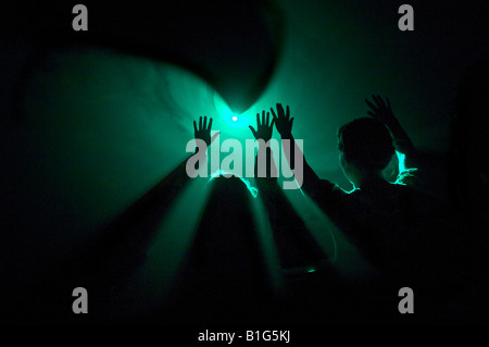 2 figures raise their hands into smoke lit by lasers - Stock Photo