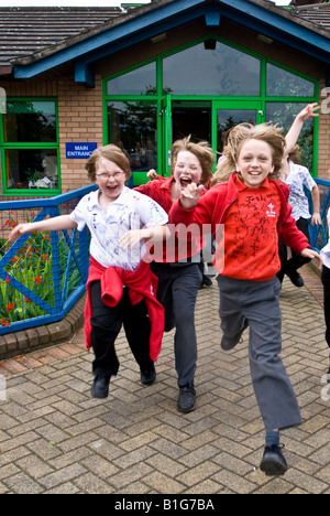 School boys race out of their school at the end of their primary years eager for the summer holidays and Big school. - Stock Photo