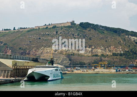 The Balearia Fast Ferry Jaume ll moored at the quayside in Barcelona Harbour overlooked by the Montjuic Fortress, - Stock Photo