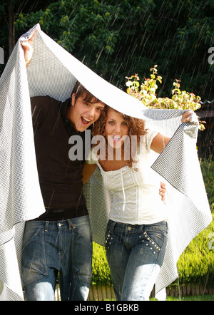 Young couple holding cloth while standing in rain - Stock Photo