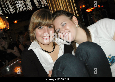two teenage girls posing for camera at night club - Stock Photo