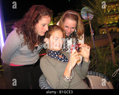 teen girls on a night out looking at digital snapshot - Stock Photo