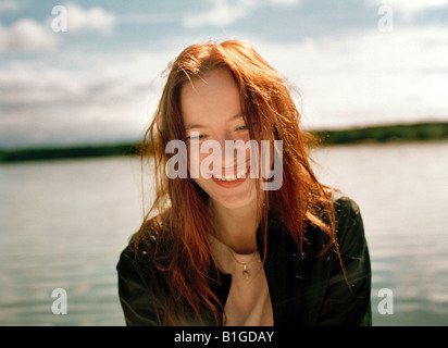 Close up of a young woman smiling near a lake Finland - Stock Photo