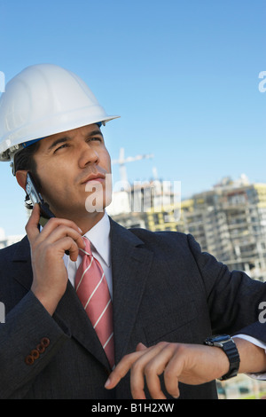 Businessman in hardhat using mobile phone, outdoors - Stock Photo