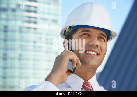 Businessman in hardhat using mobile phone outdoors - Stock Photo
